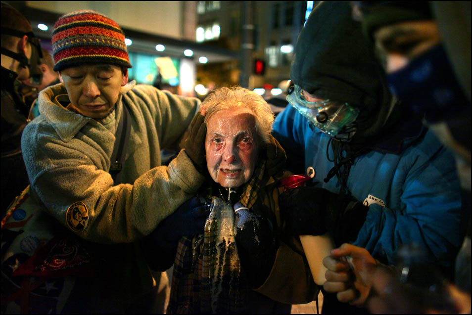 """Seattle activist Dorli Rainey, 84, is helped by fellow Occupy Seattle protestors after being hit with pepper spray Tuesday, November 15, 2011. After asking protestors to move to the sidewalk, police doused protestors with what Rainey later described as """"a fountain of pepper spray."""" Other protesters splashed a milky-solution in Rainey's face to reduce the sting of the chemical irritant. The incident sparked international outrage, a review of the department's response to the protest, and an apology from Seattle Mayor Mike McGinn."""